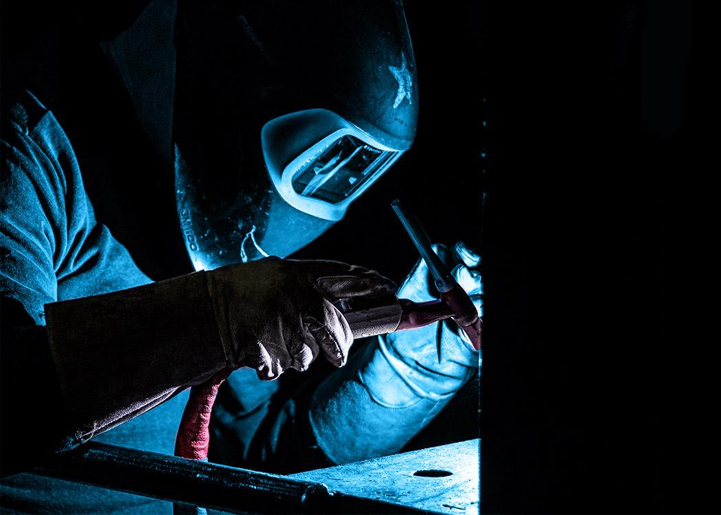 Ein Schweißer mit heruntergeklapptem Visier im Nachfolgebereich der Gießerei L+S Präzisionsguß GmbH